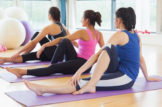 Classe fazendo a torção da medula mediana em tapetes na aula de ioga