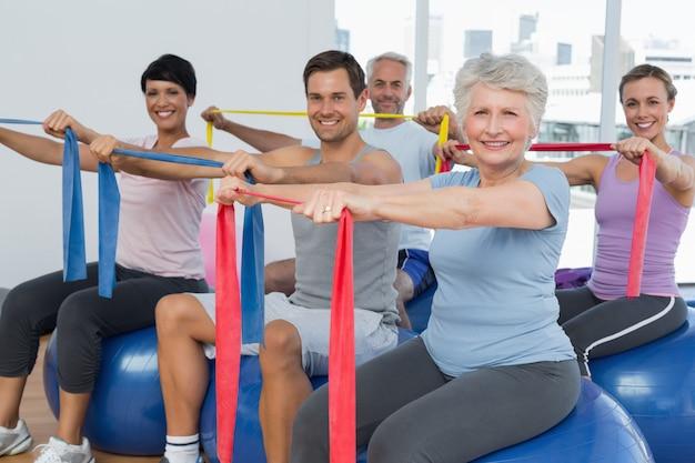 Classe segurando cintos de exercício enquanto está sentado em bolas de fitness