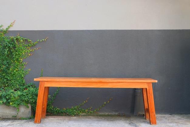 Clássico banco de madeira vintage perto da parede cinza decorar com pequenas folhas