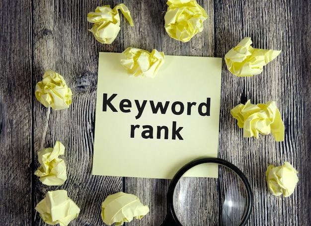 Classificação da palavra-chave - texto em folhas de notas amarelas em um fundo de madeira escuro com folhas amassadas e uma lupa