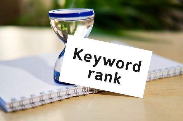 Classificação de palavras-chave para site de seo - texto de conceito de negócio em um caderno branco e um relógio de ampulheta, folhas verdes de flores