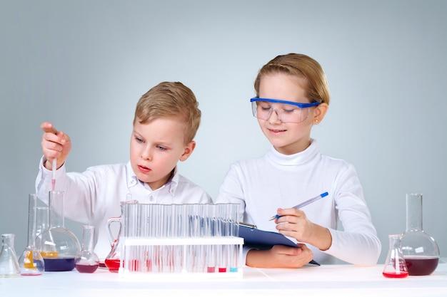 Classmates com frascos químicos e tubos de ensaio