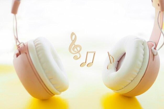 Clave de sol e notas perto dos fones de ouvido. conceito de audiolivro, podcast, música. copie o espaço.