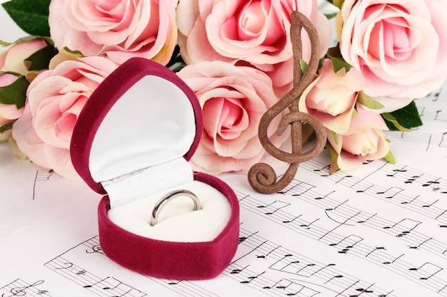 Clave de sol, rosas e caixa segurando o anel de casamento na superfície musical