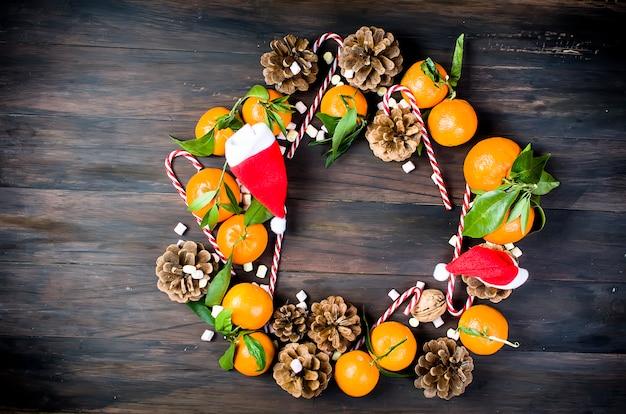 Clementina de tangerinas com folhas e brinquedos de natal em uma mesa de madeira.