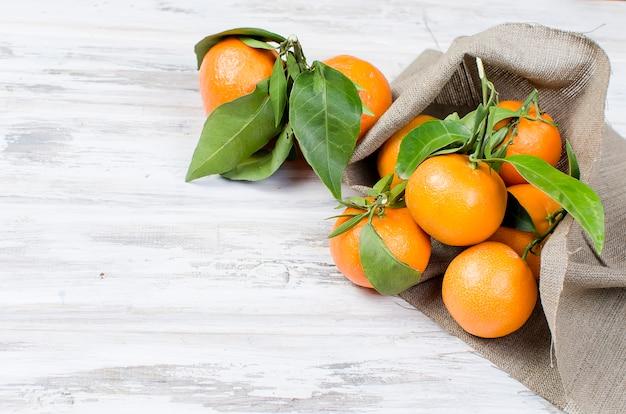Clementina de tangerinas com folhas em uma mesa de madeira.