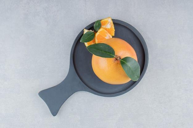 Clementina fresca e segmentos na tábua de corte preta