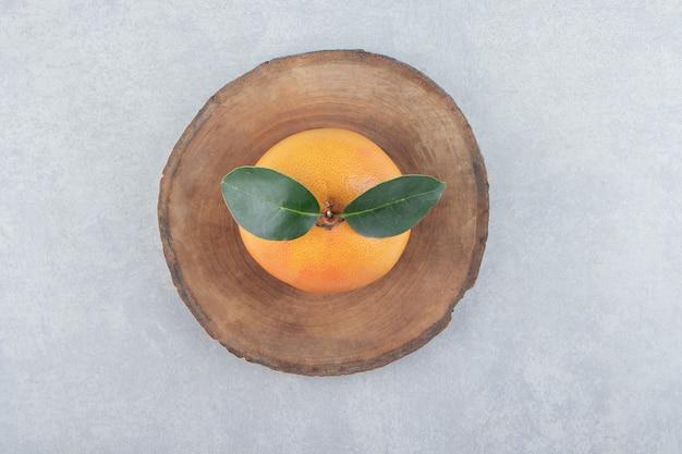 Clementina fresca única em pedaço de madeira
