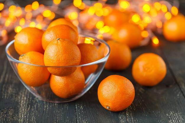 Clementina frescas da tangerina com as especiarias no fundo de madeira escuro, conceito do natal.