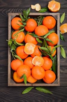 Clementina frescas da tangerina com as folhas na bandeja de madeira em de madeira escuro.