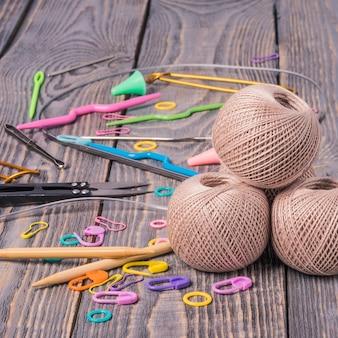 Clews do fio, agulhas de confecção de malhas, tesouras e grampos no fundo de madeira.