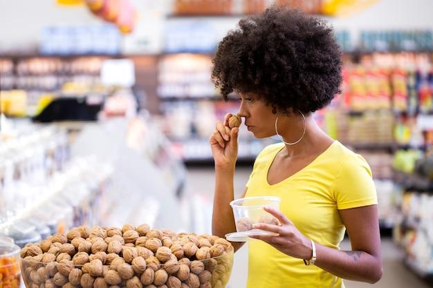 Cliente africano adulto feminino selecionando nozes no supermercado.