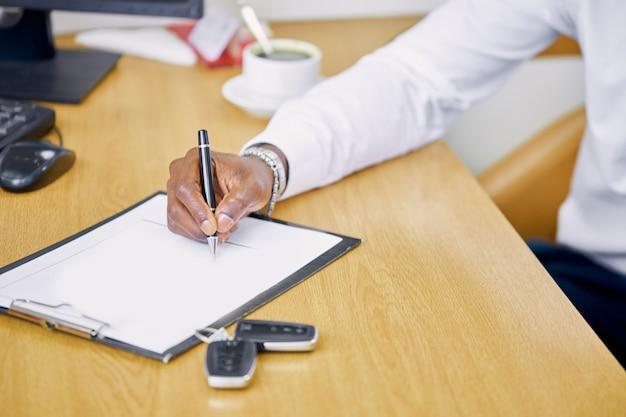 Cliente africano assinando contrato em concessionária de automóveis