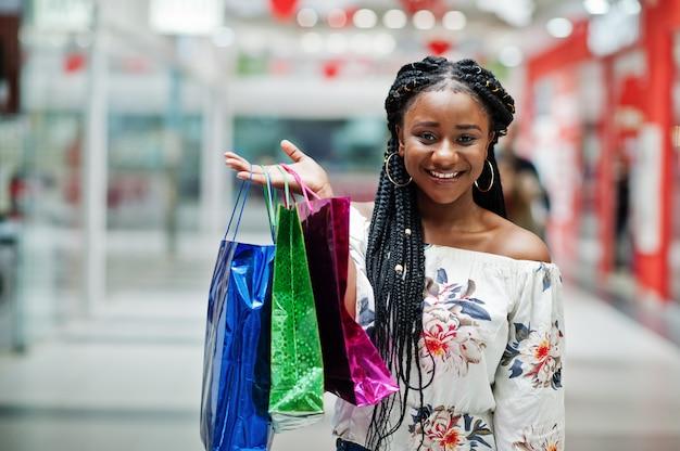 Cliente afro-americano bem vestido bonito da mulher com os sacos de compras coloridos na alameda.