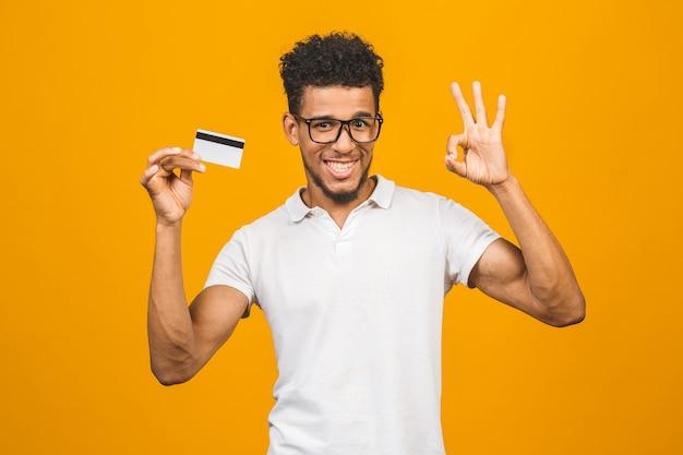 Cliente afro-americano, segurando um cartão de crédito em pé sobre um fundo amarelo isolado