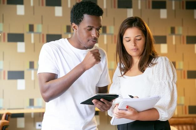Cliente afro-americano sério olhando para um caderno de mulher e segurando o tablet