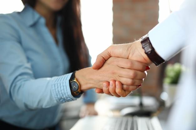 Cliente apertando a mão do agente de seguros em close do escritório