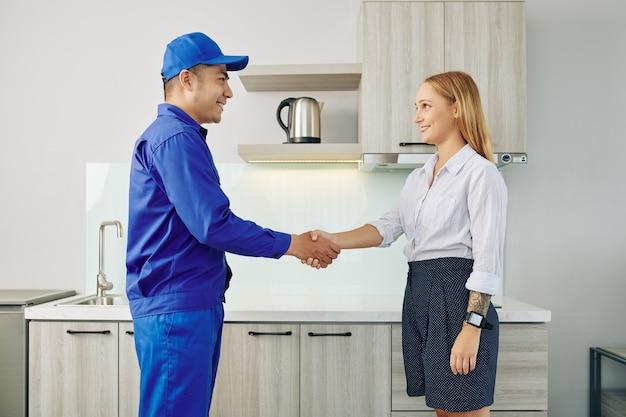 Cliente apertando a mão do técnico