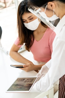 Cliente asiático escanear o menu online do código qr da garçonete com máscara e protetor facial. o cliente sentou-se na mesa de distanciamento social para um novo estilo de vida normal em um restaurante após a pandemia de coronavírus covid-19