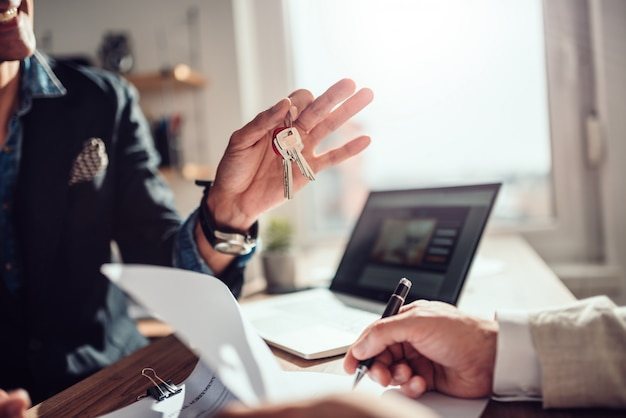 Cliente assinando contrato enquanto agente imobiliário segurando as chaves