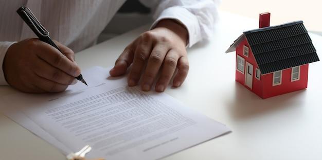 Cliente assinando contrato sobre contrato de empréstimo à habitação para nova casa