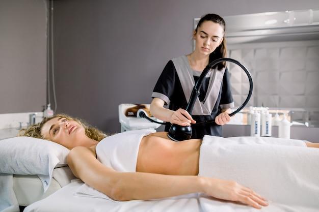 Cliente atraente jovem loira com corpo esbelto, recebendo terapia anticelulite e anti-gordura no salão de beleza de barriga.