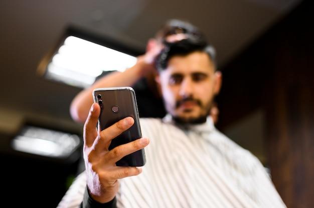 Cliente baixo ângulo, em, barbeiro, loja, olhar telefone