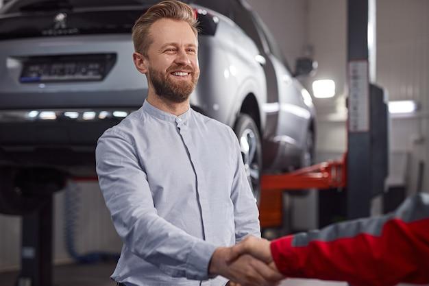 Cliente barbudo apertando a mão do técnico