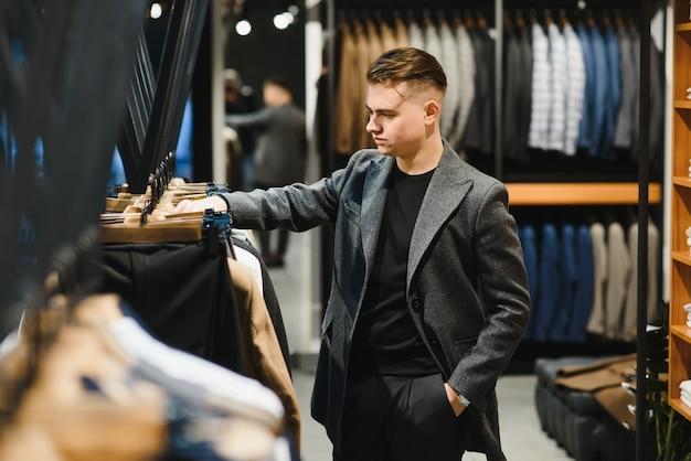 Cliente bonito jovem empresário em uma loja de fantasias inspeciona o material da manga da jaqueta no cabide.