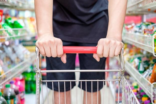 Cliente com carrinho de compras escolhendo o produto no supermercado