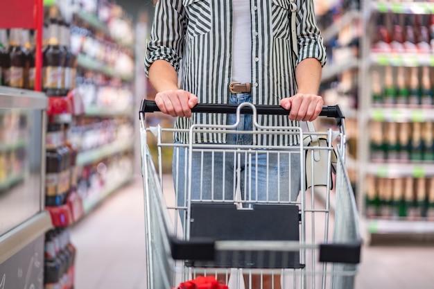 Cliente com carrinho de compras no corredor do supermercado. compra de comida no supermercado.