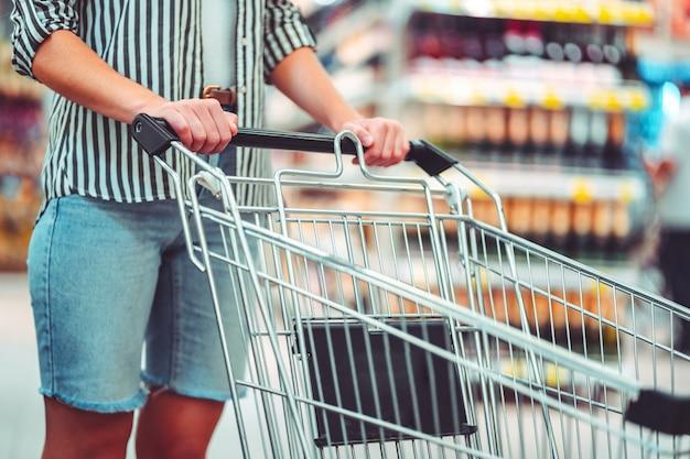 Cliente com carrinho de compras no corredor do supermercado. comprando comida no supermercado