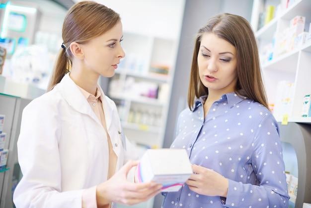 Cliente com farmacêutico lendo rótulos de medicamentos
