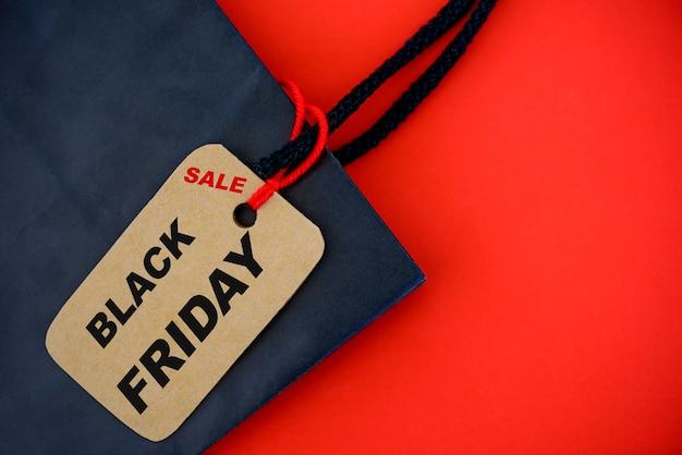 Cliente com saco de papel de sexta-feira negra e etiqueta de bilhete em fundo vermelho.