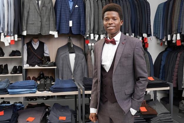 Cliente da boutique, segurando a mão no bolso da calça, posando.