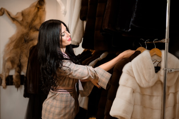 Cliente da menina que examina o casaco de pele novo na loja de panos das mulheres