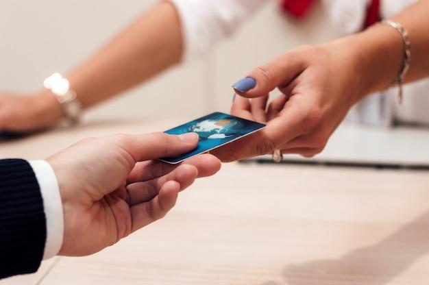Cliente da mulher que paga com o cartão de crédito na sala de exposições da forma.