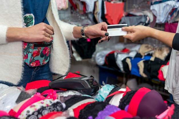 Cliente dando cartão de crédito para pagamento em loja de roupas íntimas