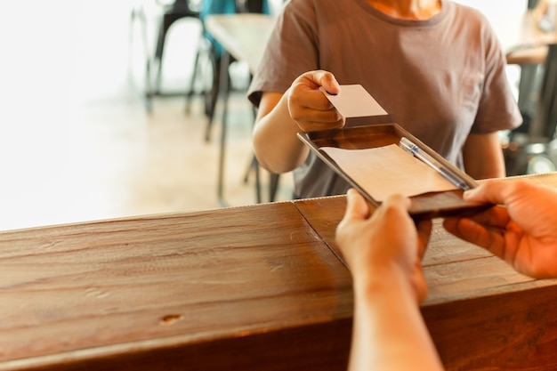 Cliente das mulheres que dá o cartão de crédito para que o empregado de mesa pague na cafetaria.