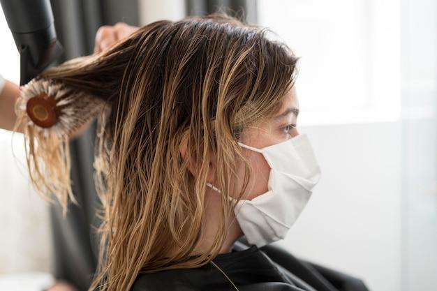 Cliente de close-up de lado no salão de cabeleireiro usando máscara médica