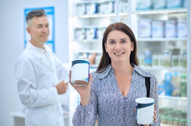 Cliente de farmácia satisfeito mostrando seus novos produtos de saúde