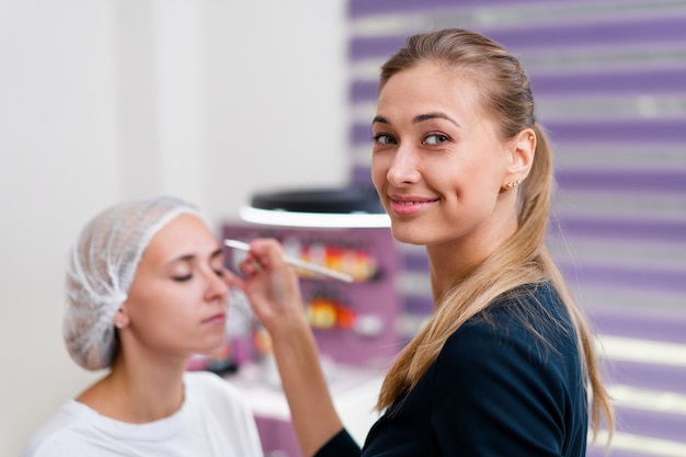 Cliente de gabinete de cosmetologia, sentado no sofá. esteticista aplica marcação nas sobrancelhas. preparação para o procedimento de maquiagem permanente sobrancelha. espaço livre. indústria da beleza