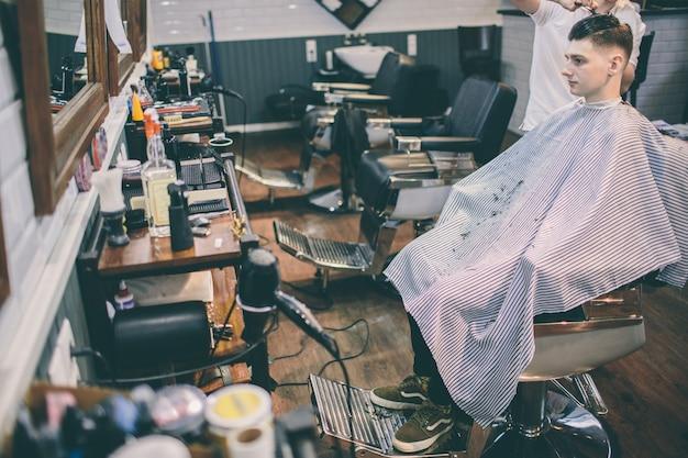 Cliente de hairstylist e plesed man com corte de cabelo olhando no espelho