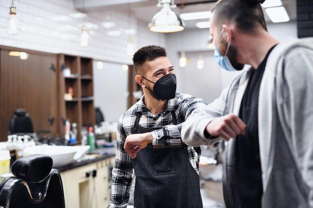Cliente de homem cumprimentando haidresser com cotovelo colisão na barbearia, coronavírus e novo conceito normal.
