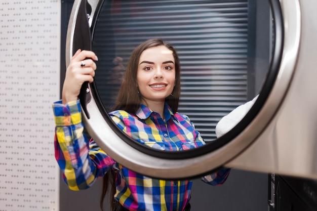 Cliente de lavanderia self-service tira as coisas do secador