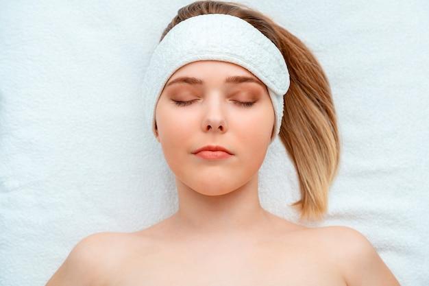 Cliente de mulher com bandana encontra-se no sofá na médica esteticista no salão de beleza. retrato modelo com pele perfeita e saudável em tratamento de beleza para o rejuvenescimento e a saúde da pele.