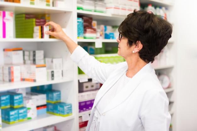 Cliente de mulher de meia idade na farmácia à procura de medicamentos