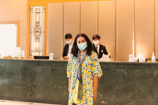 Cliente de mulher usando máscara médica em frente à recepção do hotel.