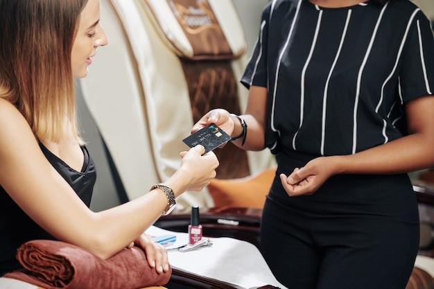 Cliente de salão de beleza pagando com cartão de crédito