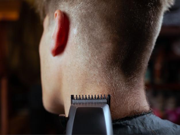 Cliente de serviço de cabeleireiro masculino, fazer o corte de cabelo usando a máquina de aparar vista traseira.